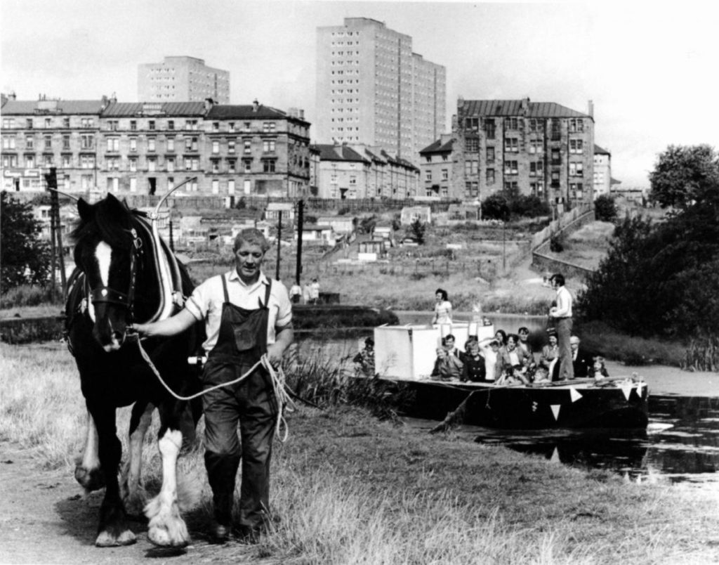 Black and white image of Maryhill around 100 years ago. People in boat on canal looking at workman pulling horse on bank. Tenement flats in the background.